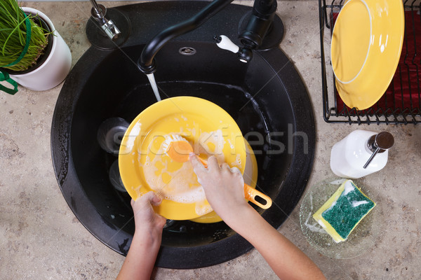 Child hands washing a plate in the kitchen sink Stock photo © ilona75