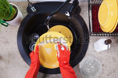 Hands with red latex gloves washing dishes in the kitchen sink Stock photo © ilona75