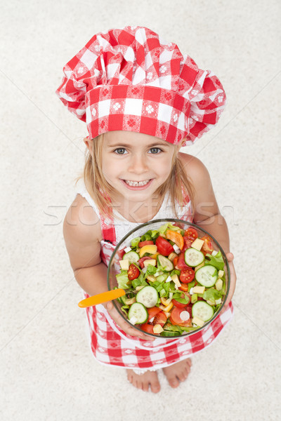 Happy little chef holding a bowl of vegetables salad - looking u Stock photo © ilona75