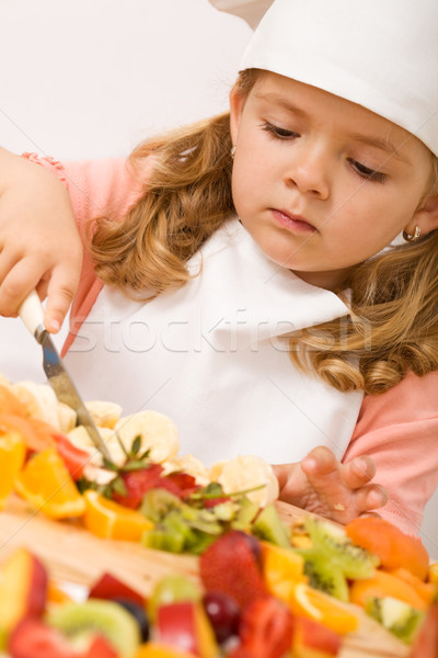 Stock photo: Little girl chef with lots of fruits