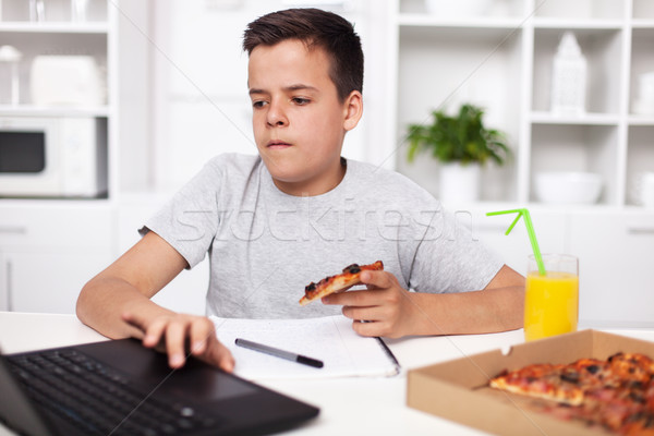 Young teenager boy working on a project having a bite of pizza a Stock photo © ilona75