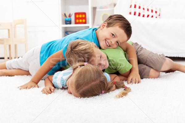 Happy wrestling kids in a pile Stock photo © ilona75