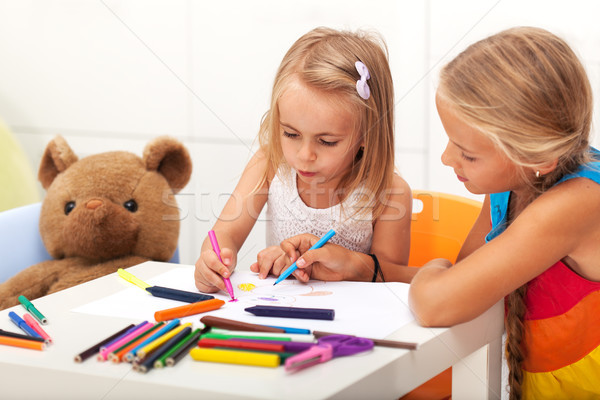 Girls drawing together - older sister helping the little one Stock photo © ilona75