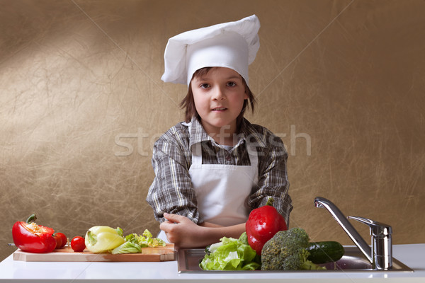 Little boy with chef hat washing vegetables Stock photo © ilona75