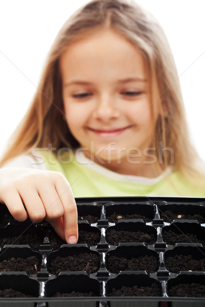 Little girl planting putting seeds into germination tray Stock photo © ilona75