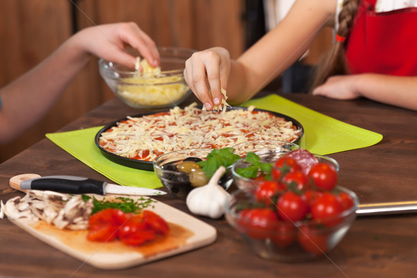 Kids making a pizza at home - spreading the shredded cheese Stock photo © ilona75