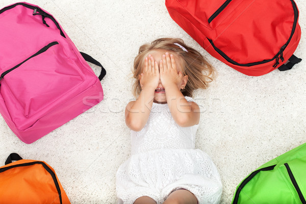 Little girl lying among colorful school bags Stock photo © ilona75