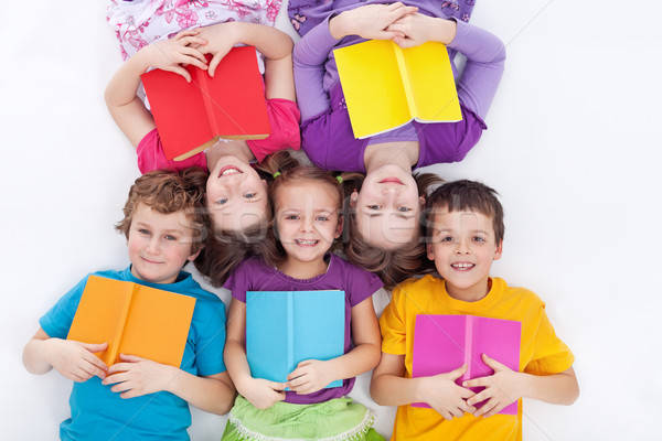 Stock photo: Happy kids laying on the floor holding books
