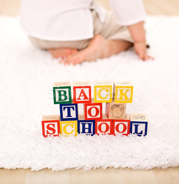 Stock photo: Child turning away from toy blocks - back to school theme