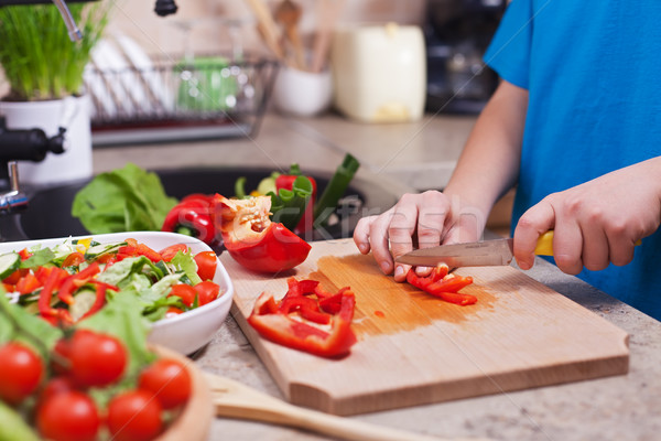 Child hands chopping vegetables on cutting board - the red bellp Stock photo © ilona75
