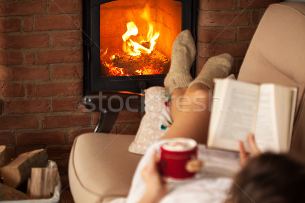 Woman enjoying free time by the fire - reading a book Stock photo © ilona75