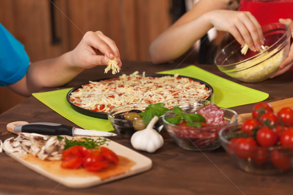 Kids making a pizza at home - putting the grated cheese on Stock photo © ilona75