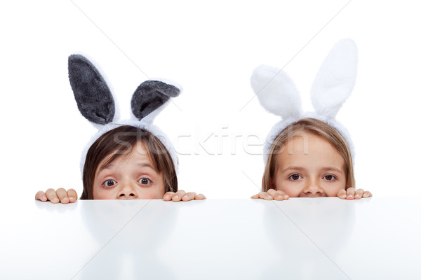 Kids with bunny ears peeking from beneath the table Stock photo © ilona75