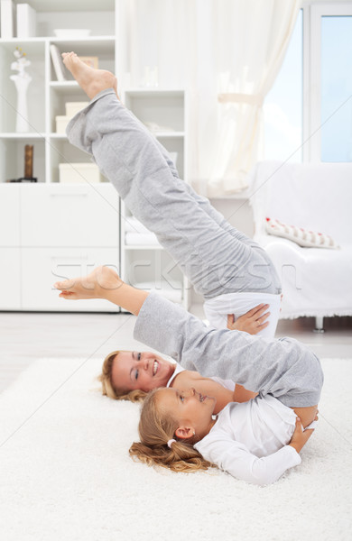Stock photo: Woman and little girl doing gymnastic exercise