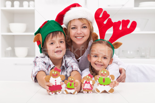 Family in christmas hats making gingerbread cookie people Stock photo © ilona75