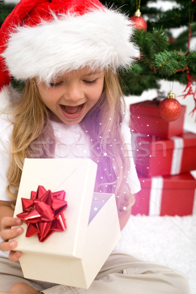 Excited little girl opening christmas present Stock photo © ilona75