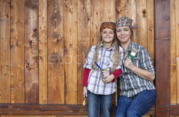 Stock photo: Little girl helping mother repainting the wood shed