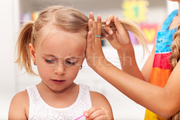 Older sister helps little girl tie her hair in plaits Stock photo © ilona75