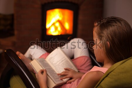 Woman lying in cozy warmth on a couch in front of fireplace Stock photo © ilona75