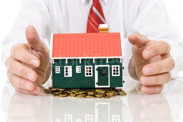 Stock photo: House on golden coins pile with businessman hands