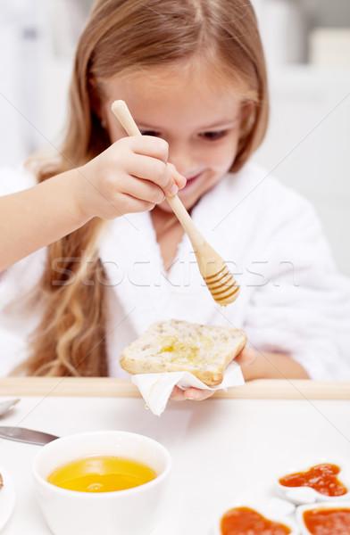 Zoete ochtend meisje eten honing brood Stockfoto © ilona75