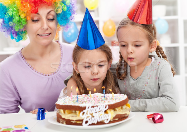 Birthday girl blowing out candles on a cake Stock photo © ilona75