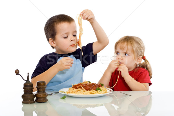 Two kids eating pasta with their hands Stock photo © ilona75