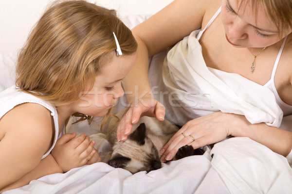 Little girl and her mother stroking a kitten Stock photo © ilona75
