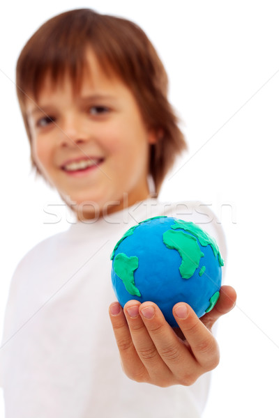 Smiling boy holding modelling clay earth Stock photo © ilona75