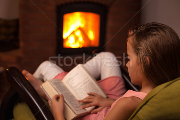 Jeune fille séance cheminée lecture livre Photo stock © ilona75
