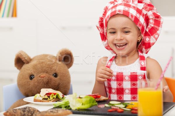 Kicsi boldog lány falatozó plüssmaci ül asztal Stock fotó © ilona75