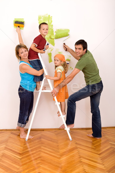 Happy family with painting utensils repainting their home Stock photo © ilona75