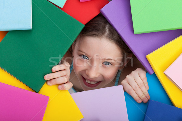 Young girl emerging from beneath books Stock photo © ilona75