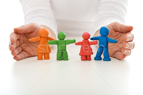 Clay people family protected by woman hands Stock photo © ilona75