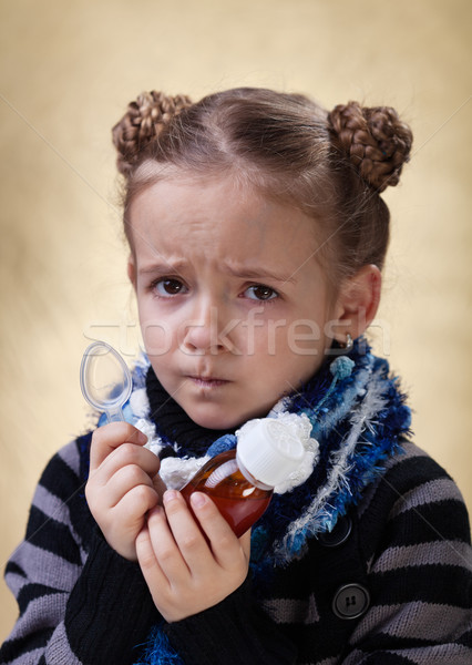 Little girl with cough medicine having a worried look Stock photo © ilona75