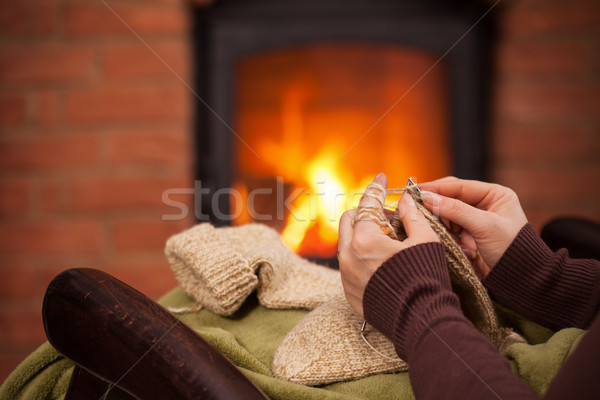 Woman knitting warm wool socks in front of fireplace - closeup Stock photo © ilona75