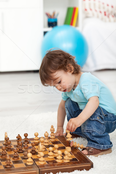 Stock photo: Toddler boy playing with chess pieces