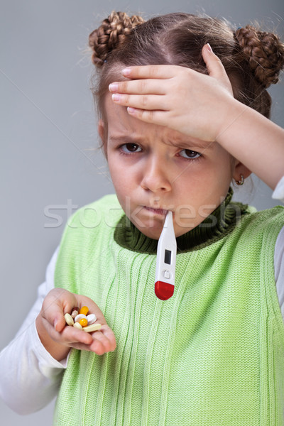 Sick little girl with pills and thermometer Stock photo © ilona75