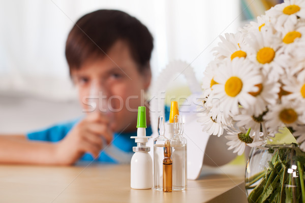 Stock photo: Blurry boy using inhaler device with medication in the foregroun