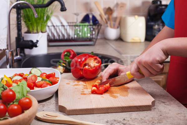 Child hands chopping a red bellpepper for a fresh vegetables sal Stock photo © ilona75