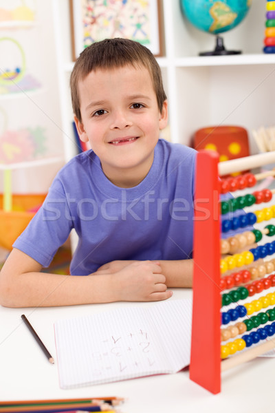 Happy kid solving math exercise Stock photo © ilona75