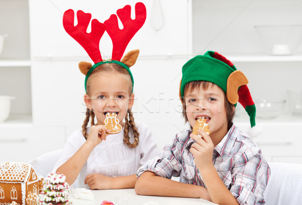 Kids with christmas hats eating gingerbread cookies Stock photo © ilona75