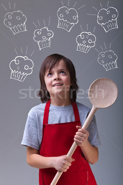 Young chef with apron and large wooden spoon Stock photo © ilona75