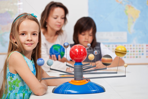 Kids study the solar system under their teacher supervision Stock photo © ilona75
