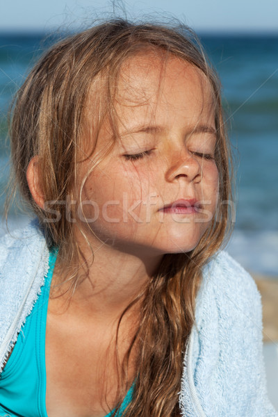 Little girl soaking up the sun on the windy sea shore Stock photo © ilona75