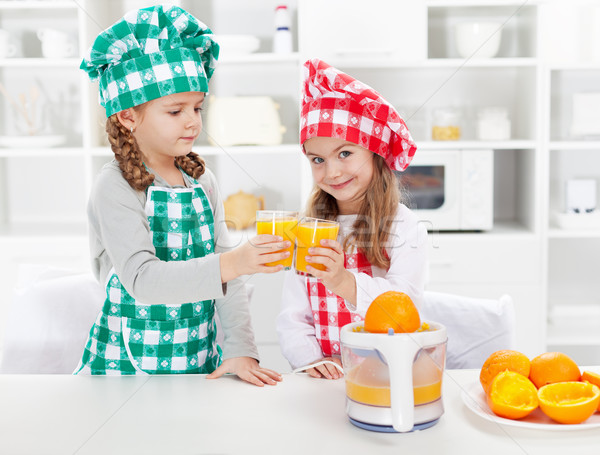 Little chefs making fresh orange juice in the kitchen Stock photo © ilona75