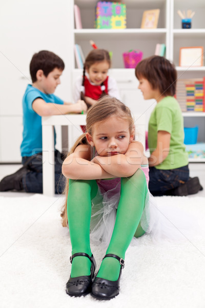 Sad little girl sitting excluded by the other kids Stock photo © ilona75