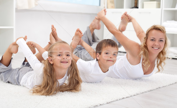 Family doing stretching exercises at home Stock photo © ilona75