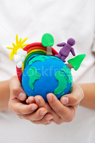 Modelling clay earth with rainbow and trees in child hands Stock photo © ilona75