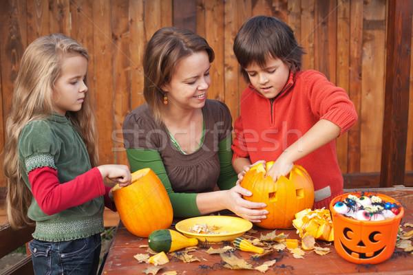 Woman helping kids to carve jack-o-lanterns Stock photo © ilona75
